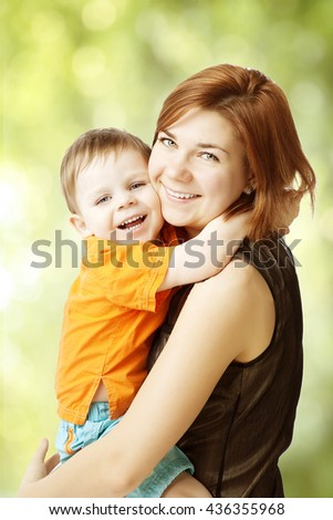 Mother hugging her son. Happy woman and kid smile. Girl and child playing and laughing. Baby on hands at mum - stock photo