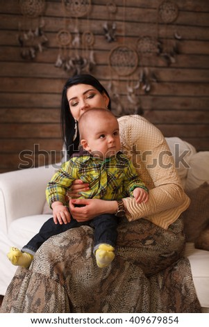 Mother hugging her son, the child poses a funny face. Cute little boy making grimaces. home inside - stock photo