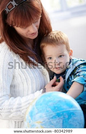 Mother hugging little boy, globe front of them.? - stock photo