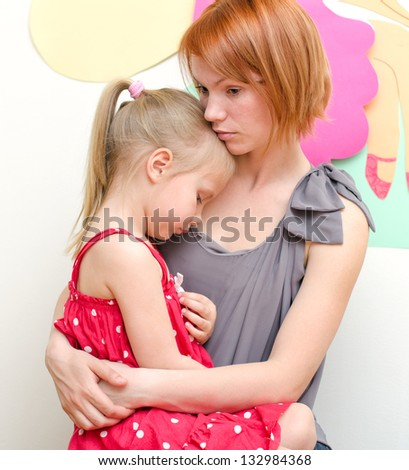 Mother huging her sad child - stock photo