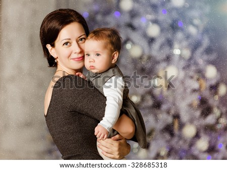 Mother hugs little cute chubby baby girl in a gray dress on the white background of Christmas tree in New year - stock photo
