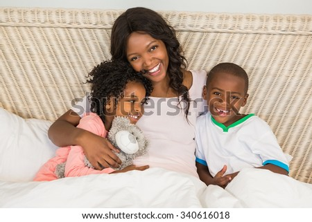 Mother in bed with children at home - stock photo