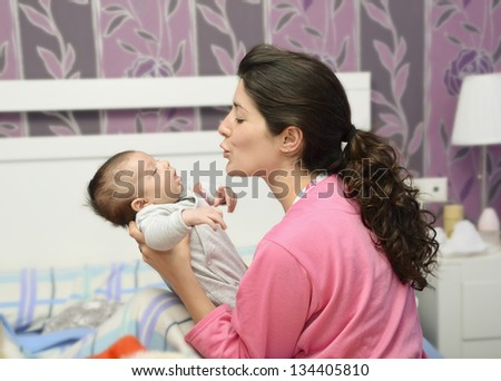 Mother in bedroom with pajama and his newborn little baby. - stock photo
