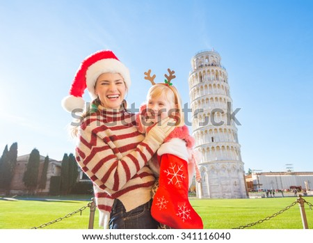 Mother in Christmas hat holding daughter in funny reindeer antlers pulling out gift from Christmas sock. Leaning Tour of Pisa in background. They spending exciting Christmas time traveling Italy - stock photo
