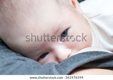 Mother in special clothes for feeding nursing her child close-up view from above - stock photo