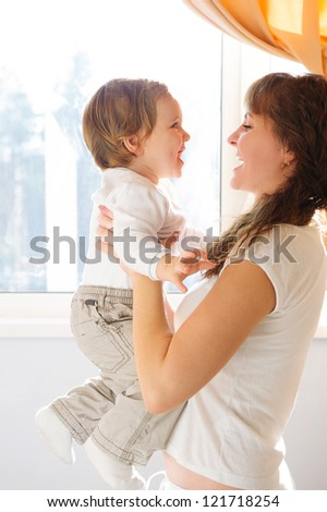 Mother in white clothes holding little son against window - stock photo