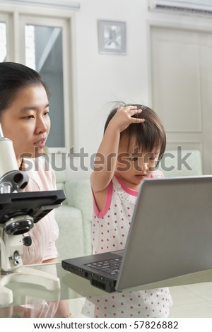 Mother introduce technology to her daughter with laptop and microscope