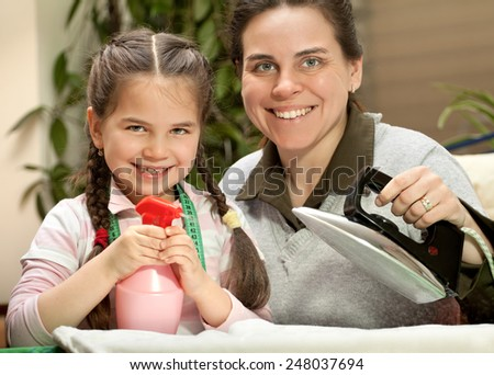 Mother ironing with little daughter - stock photo