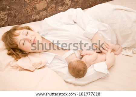 Mother is breast feeding a newborn baby lying down in bed. The symbol of happiness and motherhood. Lucky family is sleeping. - stock photo