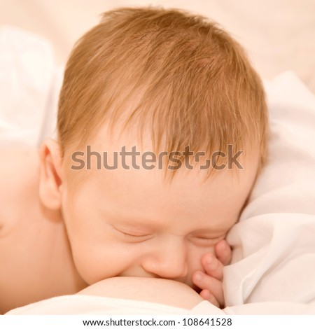 Mother is breast feeding a newborn baby. Suckling eating with his hand under his cheek. - stock photo