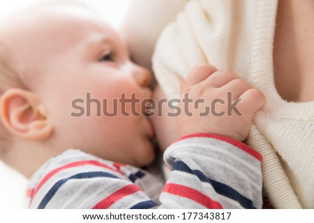 Mother is breast-feeding her baby - focus on baby hand