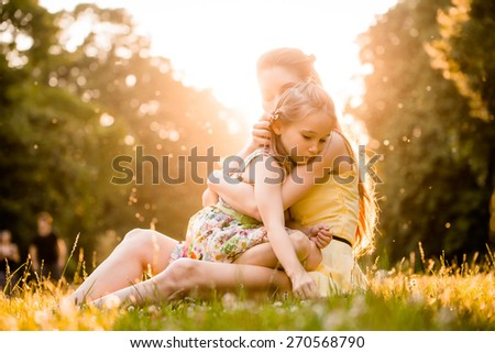 Mother is cuddling her worried child outdoor in nature - stock photo