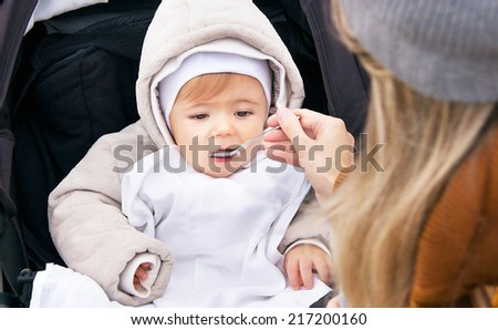 Mother is feeding nine month baby boy from a spoon. Child has healthy food outdoor. Porridge is for healthy eating child (kid). Caucasian male model is sitting in the baby buggy (pram, pushchair).  - stock photo