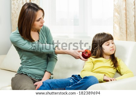 Mother is giving fruit to her daughter to eat but she is very angry,she don`t like fruit,I don`t want to eat fruit! - stock photo