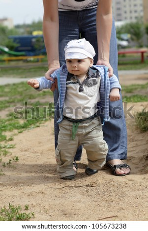 Mother is helping her boy taking his first steps