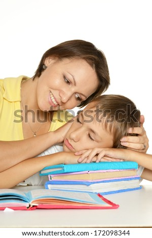 Mother is helping her son doing homework. Son fell asleep - stock photo