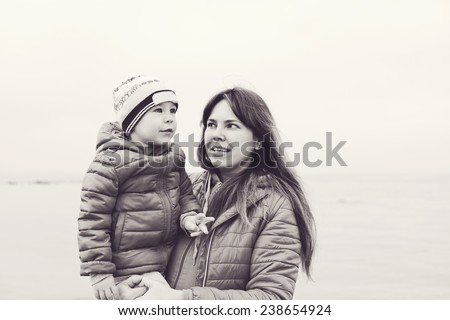 mother is holding her toddler  son outdoors - stock photo
