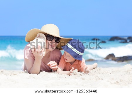 mother is lying with her son at a tropical beach and listening to a shell - stock photo