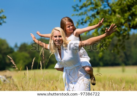 Mother is playing with daughter in meadow on a summer day - stock photo