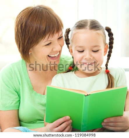 Mother is reading book for her daughter, indoor shoot