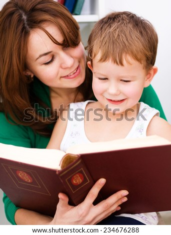 Mother is reading book with her son, indoor shoot - stock photo