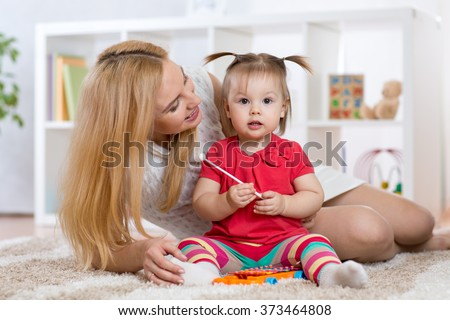 Mother is showing child how to play xylophone toy - stock photo