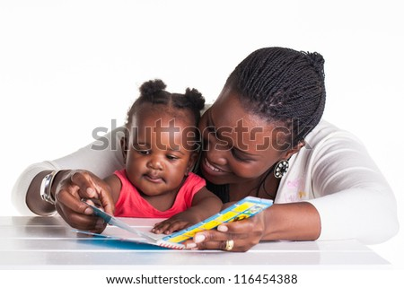 Mother is showing some pictures in a book to her daughter. - stock photo