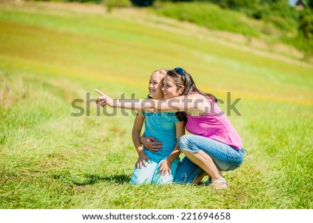 Mother is showing something in distance to her child in nature on sunny summer day