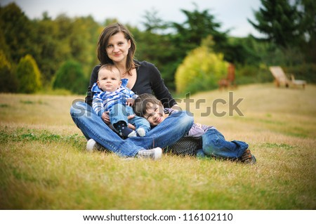 Mother is sitting in a park with her sons - stock photo