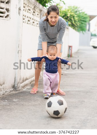mother is teaching his son for playing football.