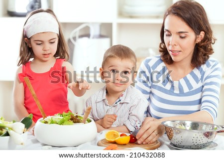 Mother is teaching their kids how to make salad