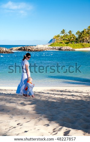 Mother is walking with the son on Hawaiian beach - stock photo
