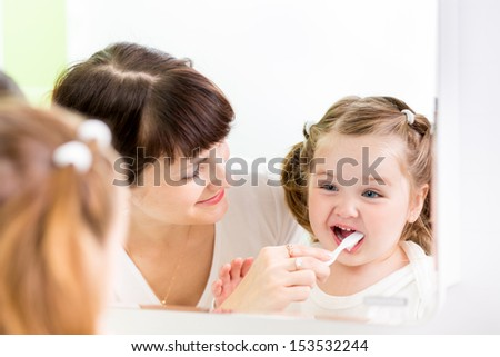 mother kid brushing kid teeth - stock photo