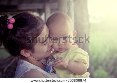 Mother kiss cute little boy with love in sweet soft color filter