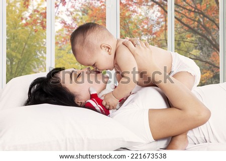 Mother kiss her baby girl on bedroom with autumn tree background on the window - stock photo