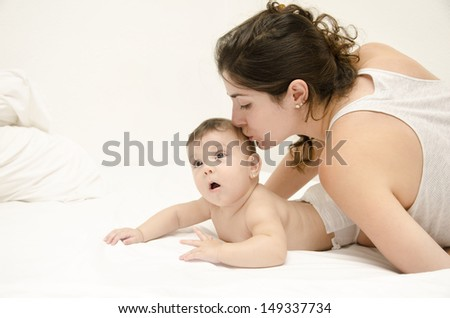 Mother kiss her daughter in white bedroom. - stock photo