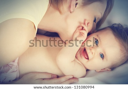 mother kissed her little baby, close-up