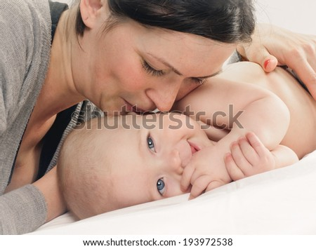mother kissed her little baby, close-up on white background - stock photo