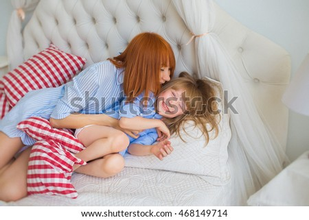 Mother kisses her little daughter on a bed in the morning