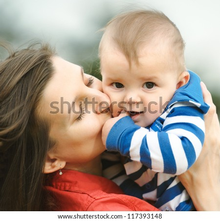 Mother kisses her son - stock photo