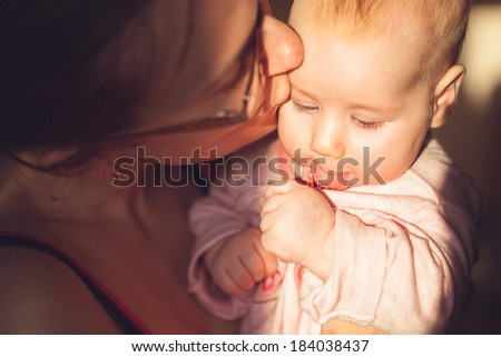 mother kisses the child. bright sunny weather.