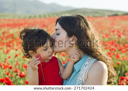 Mother kissing baby at poppies field in spring day