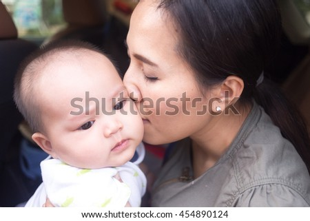 mother kissing baby cheek