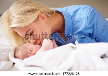 Mother Kissing Baby Girl As They Lie In Bed Together
