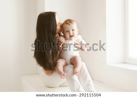 Mother kissing baby in white room at home near window - stock photo
