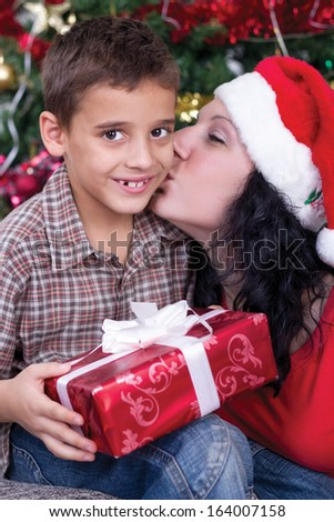 mother kissing boys at Christmas night - stock photo