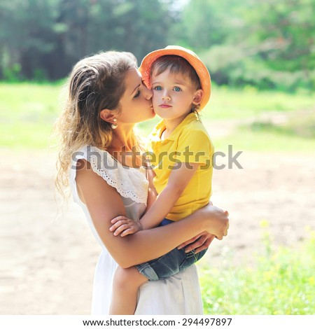 Mother kissing child outdoors in sunny summer day