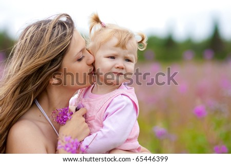 Mother kissing daughter in meadow outdoor - stock photo