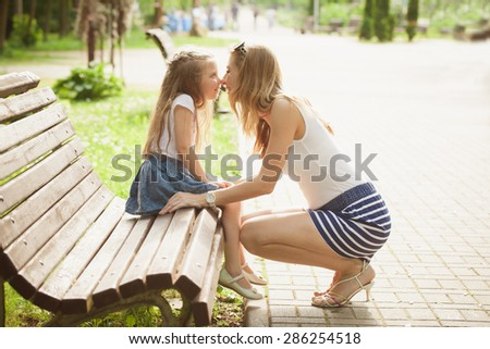 mother kissing daughter in the park - stock photo