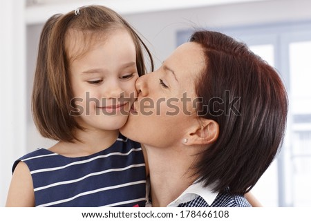 Mother kissing happy little daughter's face. - stock photo